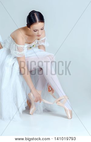Professional ballerina putting on her ballet shoes on the gray background