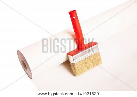 Brush and roll of wallpaper isolated on white background