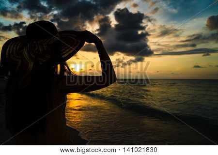 Tourist woman watching sunset at tropical ocean beach