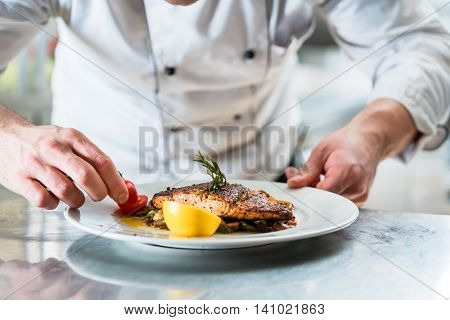 Chef with diligence finishing dish on plate, fish with vegetables
