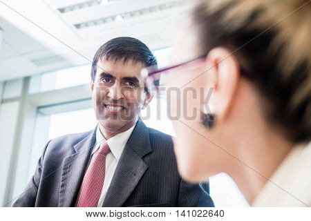 Indian business CEO smiling at his secretary in company office