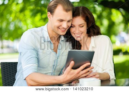 Smiling couple using a tablet while sitting outdoors