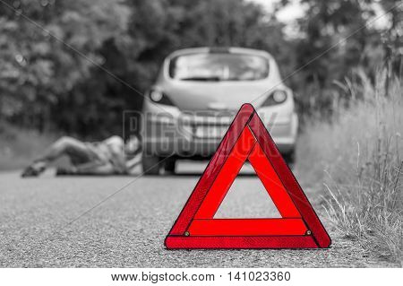 Driver Lying Under The Broken Car And Red Triangle