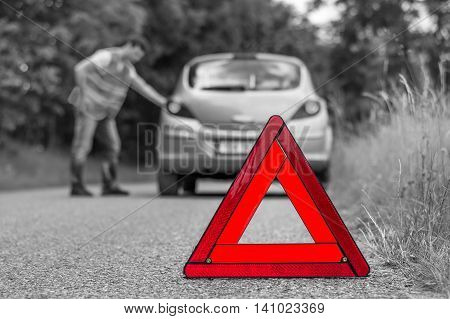 Broken Car On The Road And Unhappy Driver With Red Triangle