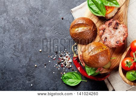 Homemade burgers with beef, cheese, tomatoes, cucumber and basil on cutting board. Top view with copy space