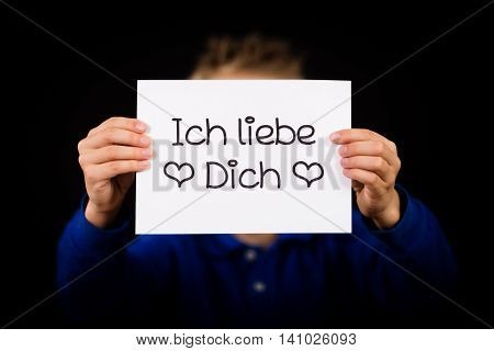 Studio shot of child holding a sign with German words Ich liebe Dich - I Love You