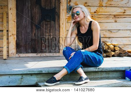 Girl sitting on a porch in a wooden house. Young blonde with sun glasses. Smotrt away holding hand on chin