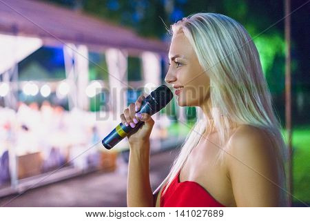 Young girl with a radio microphone in hand stands on the stage of the evening red dress looking away. Long blond hair evening event outside in the park