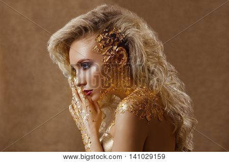 A beautiful woman blond wavy hair professional make-up the color of gold gold jewelry beauty fashion model clean skin close-up portrait . Body gold pattern. Photographed in studio on a gold background