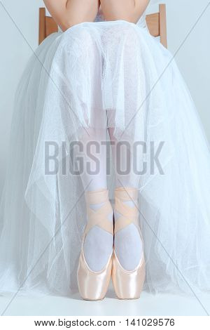 Professional ballerina resting after the performance and sitting with her ballet shoes on the gray background