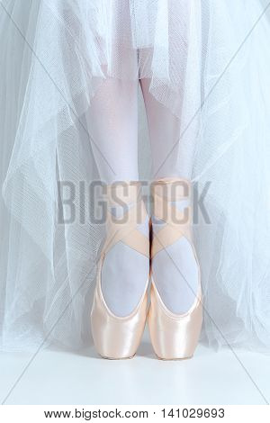 The close-up feet of young ballerina in the pointe shoes