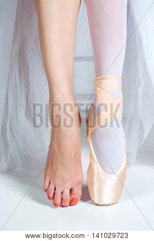 The close-up feet of young ballerina in the pointe shoes and without it