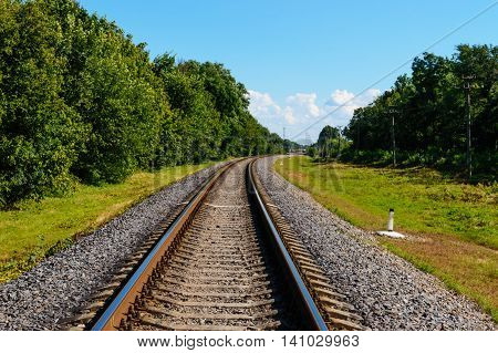 The railway goes to horizon on both sides of the green dense forest.
