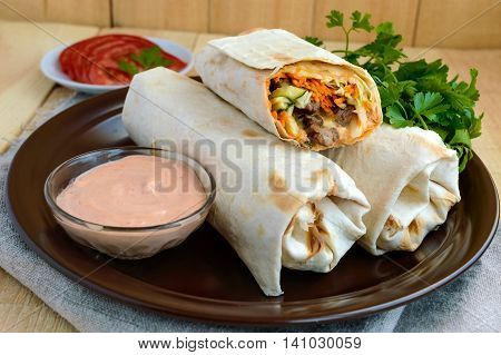Shawarma - Middle East (Arabic) dish of pita (lavash) stuffed with: grilled meat sauce vegetables