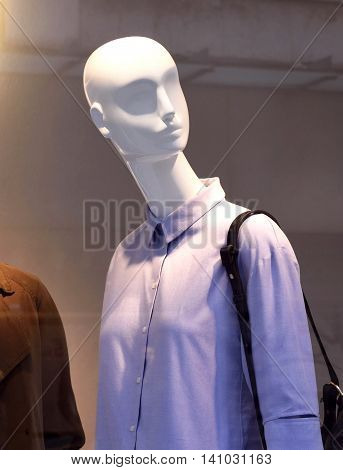Female plastic mannequins behind a fashion store window. Two white display dummies. View through a shop window.