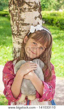 cute little girl with big gray eyes at the park with a toy in the hands