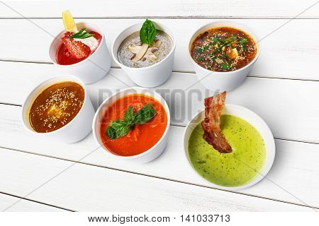 Variety of restaurant hot dishes, healthy food. Japanese miso soup, asian fish soup, russian borscht, english pea soup with bacon, mushroom soup, spanish gazpacho at white wood