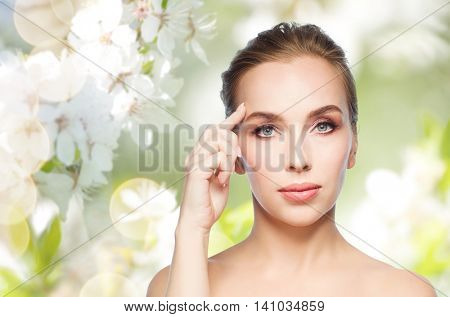 beauty, people and plastic surgery concept - beautiful young woman showing her forehead over natural spring cherry blossom background