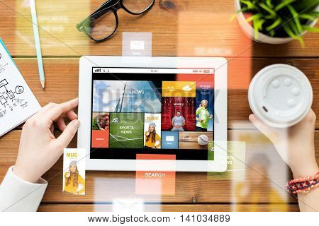 business, education, technology, people and mass media concept - close up of woman with internet news application on tablet pc computer screen and coffee on wooden table
