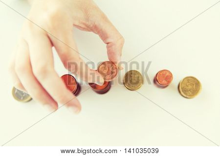business and money saving concept - close up of female hand putting euro coins into columns in office