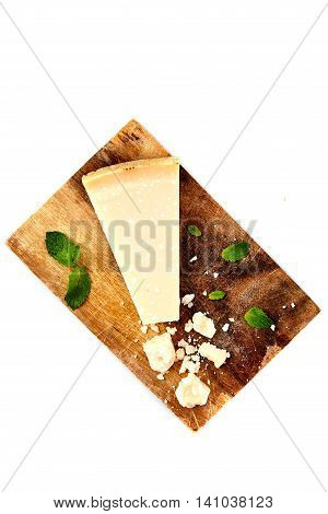 Top view of pieces of parmigiano reggiano or parmesan cheese on wood board isolated on white. Parmesan is hard cheese uses in pasta dishes, soups, risottos and grated over salads.