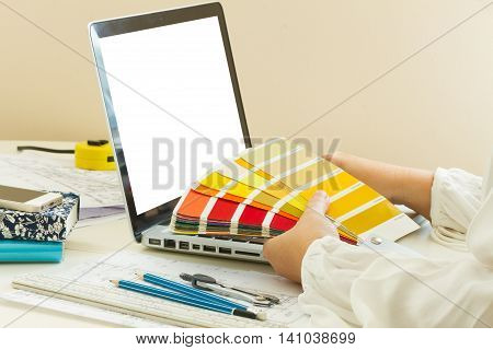 designer's working table - dhands of esigner holding colour guide, copy space on emptyy screen
