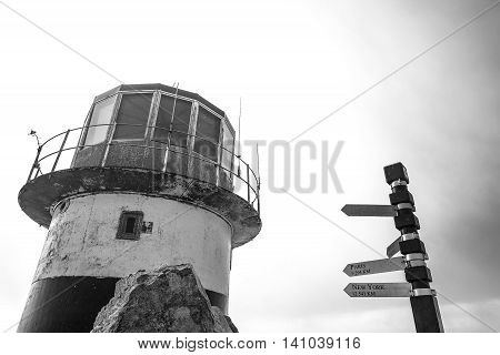 Retired lighthouse and distance sign located at Cape Point in South Africa