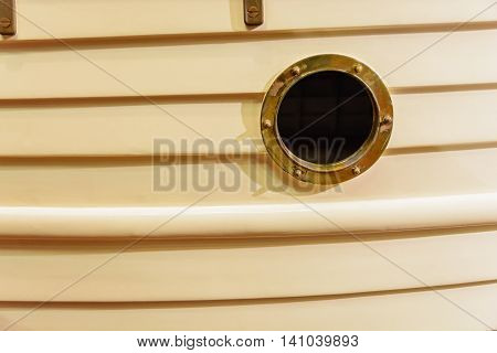 ship window or porthole on wooden biege wall
