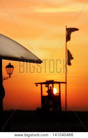 Marine Lifeguard Tower With Black Male Silhouette On Sunset Background