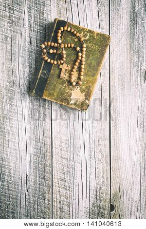 rosary beads and holy bible on old wooden table.