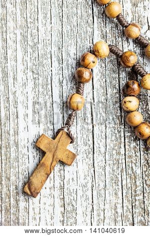 The wooden rosary beads on old table.