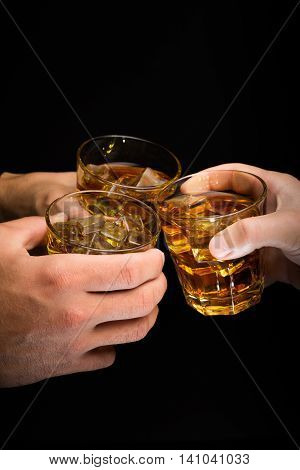 Closeup of Hands Toasting with Whiskey Glasses