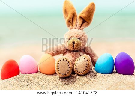 Easter bunny and color eggs on the sandy beach