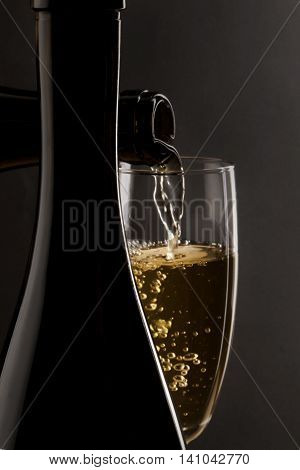 Champagne being poured into a champagne flute with a dark background