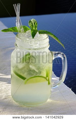 Close Up Of Misted Glass Mason Jar With Mojito Cocktail On The Table Popular Summer Drink Mixed With Rum Soda Water Cracked Ice Lime Wedges And Mint Sprig