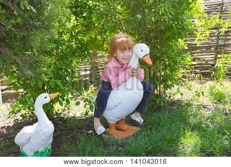Cheerful red-haired girl sitting on an artificial duck