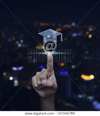 Hand pressing e-learning icon over blurred light city tower background Study online concept