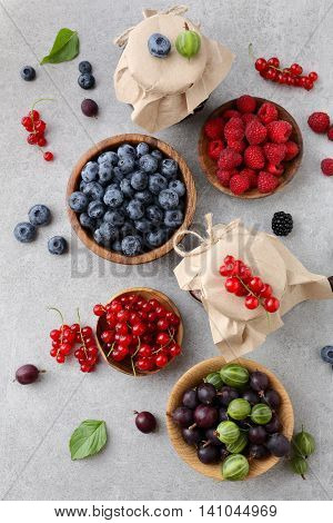 Mixed Fresh Ripe Berries In Bowl And Jam On Slate Background