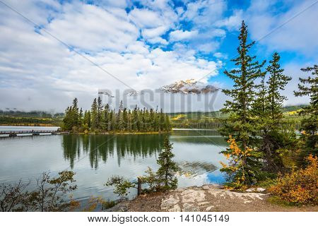 The concept of active tourism and recreation. Small island in Pyramid Lake. Cold autumn day in the Canadian Rockies