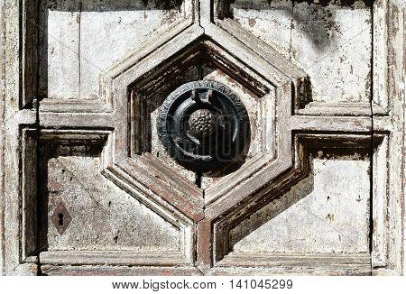 Antique door knocker. Old styled light door