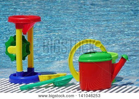 Large Group Of Wet Beach Plastic Child Toys At The Poolside Near Water Surface. Colorful Watering Can Water Mill Bucket Scoop Shovel Molds