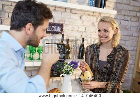 Young woman having icecream in cafeteria with boyfriend, smiling happy.