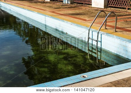 Old abandoned swimming pool with dirty water