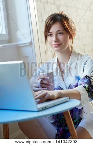 Young woman sitting on floor, using laptop computer.