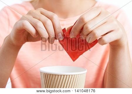 Close Up Of Woman Adding Artificial Sweetener To Coffee