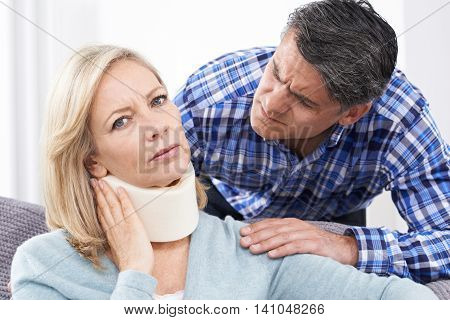 Husband Comforting Husband Suffering With Neck Injury
