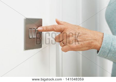 Close Up Of Woman Turning Off Light Switch