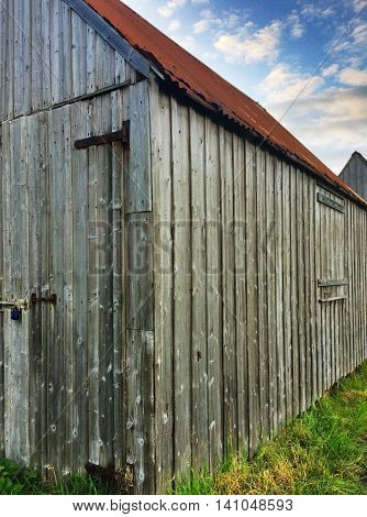 Rustic fishing shed with cloudy blue sky