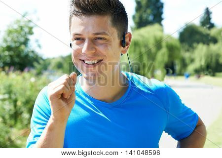 Close Up Of Young Man Running In Park Listening To Music