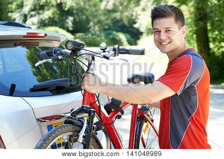 Cyclist Taking Mountain Bike From Rack On Car